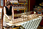 Bagerjomfru skærer franskbrød - Woman cutting a giant white bread in France Alsace Ribeauville