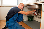 Vvs-montør - Heating and sanitary technician repairing the leaky pipes under the kitchen sink