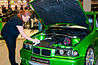 Ung kvinde rengør bil - Young female cleaning her racing green BMW car